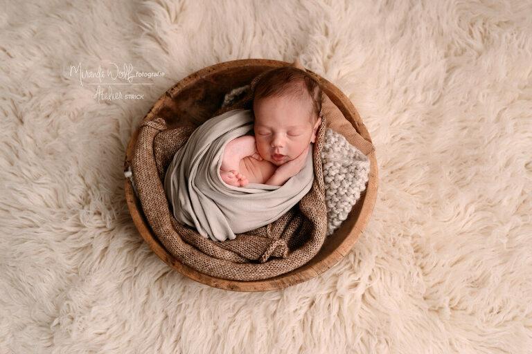 baby in houten schaal